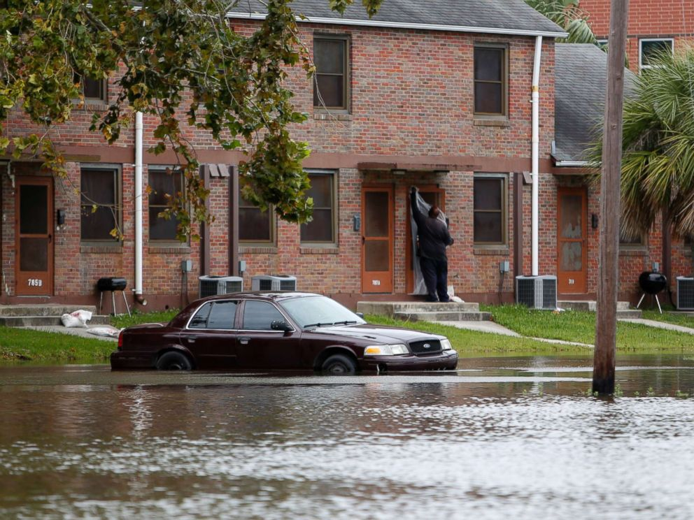 PHOTO: A Charleston, S.C. resident puts plastic up over his apartment door as a car rests in floodwaters near East Bay Street in Charleston, S.C., Sept. 10, 2017.