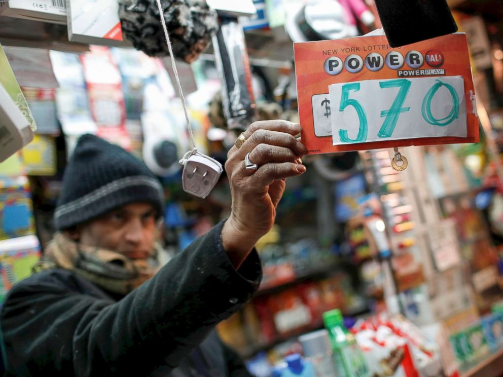 PHOTO: A vendor selling lottery tickets hangs a sign for the Powerball drawing at a press kiosk in midtown Manhattan on January 5, 2018.