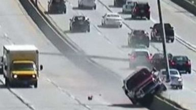 Out-of-control truck smashes light poles after climbing highway median: Video